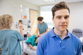 Portrait of Man with Birthing Wife in Background — Stock Photo