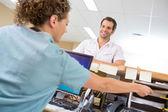 Man Looking At Nurse Working At Reception Desk — Stock Photo