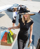 Rich Woman Carrying Shopping Bags While Boarding Private Jet — Stock Photo