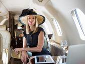 Mujer rica que se sienta en el jet privado — Foto de Stock