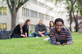 Student With Digital Tablet On Grass At Campus Park — Stock Photo