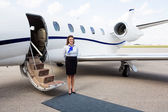 Airhostess Standing By Private Jet — Stock Photo