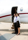 Stewardess And Pilot Standing Against Private Jet — Stock Photo
