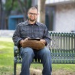 Smiling Male University Student Sitting On Bench — Stock Photo #40080619