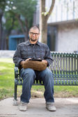 Smiling Male University Student Sitting On Bench — Stock Photo