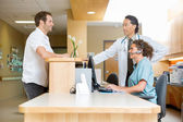 Patient With Doctor And Nurse At Reception Desk — Stock Photo