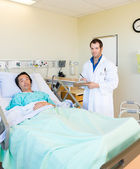 Doctor Writing On Clipboard By Patient's Bed In Hospital — Stock Photo