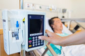 Nurse Operating IV Machine While Patient Lying On Bed — Stock Photo