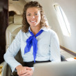 Gelukkig stewardess met laptop in prive-jet — Stockfoto #40295513