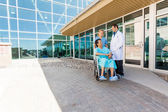 Nurse And Doctor Looking At Patient On Wheelchair At Courtyard — Stock Photo