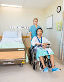Male Patient Sitting On Wheelchair While Nurse Assisting Him — Stock Photo