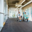 Stock Photo: Medical Team Pushing Patients On Wheelchairs At Hospital Corrido