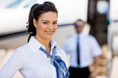 Stewardesses Smiling With Pilot And Private Jet In Background — Stock Photo