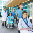 Nurses Assisting Patients On Wheelchairs Outside Hospital Buildi — Stock Photo #40683371