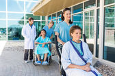 Nurses Assisting Patients On Wheelchairs Outside Hospital Buildi — Stock Photo