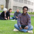 Portrait Of Student Sitting On Grass At Campus Park — Stock Photo #40696735