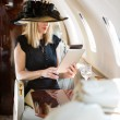 Stock Photo: WomUsing Digital Tablet In Private Jet