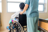 Nurse Holding Patient's Wheelchair's Handle By Window — Stock Photo