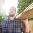 Carpenter Carrying Planks While Looking Away At Site — Stock Photo