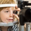Stock Photo: Optician's Hand Checking Boy's Eye With Lens