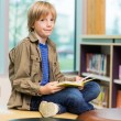 Happy Boy Reading Book In Library — Stock Photo