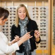 Stock Photo: WomAssisting Customer In Selecting Glasses