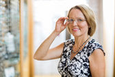 Happy Woman Trying On Eyeglasses In Store — Stock Photo