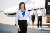 Airhostess With Hand On Hip Standing At Airport Terminal — Stock Photo