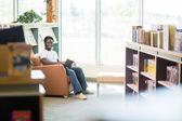 Uśmiechający się uczniem czytanie książki w bibliotece — Stockfoto