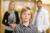 Confident Boy With Optometrist And Mother At Store — Stock Photo