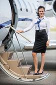 Hôtesse de l'air debout sur une échelle de jet privé — Photo