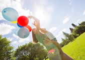 Mother And Daughter Holding Balloons In Park — Stock Photo
