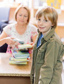 Boy With Librarian Scanning Books At Library Counter — Stock Photo