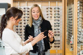 Woman Assisting Customer In Selecting Glasses — Stock Photo