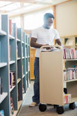 Librarian With Trolley Of Books Working In Library — Stock Photo