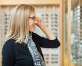Woman Trying On Glasses In Optician Store — Stock Photo