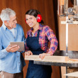 Carpenter With Senior Colleague Using Digital Tablet — Stock Photo #50084605