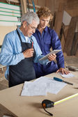 Carpenter Using Digital Tablet With Coworker — Stock Photo