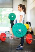 Female Athlete Lifting Barbell At Gym — Stock Photo