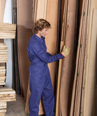Carpenter Arranging Wooden Planks In Workshop — Stockfoto