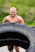 Male Athlete Doing Tire-Flip Exercise — 图库照片