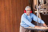 Senior Carpenter Cutting Wood With Bandsaw — Stock Photo