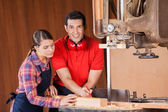 Carpenter Measuring Wood With Coworker In Workshop — Stock Photo