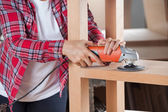 Midsection Of Carpenter Using Sander On Shelf — Stock Photo