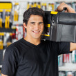Man Carrying Toolbox On Shoulder In Hardware Store — Stock Photo #50975463