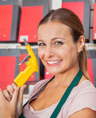 Saleswoman Holding Air Compressor Hose In Shop — Stock fotografie