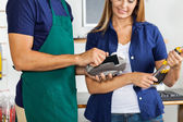 Worker Swiping Credit Card With Woman Holding Screwdriver Set — Stock Photo