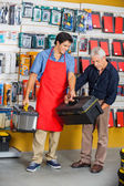 Salesman Assisting Man In Selecting Toolbox At Store — Stock Photo