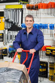 Mature Worker Pushing Trolley In Hardware Shop — Foto Stock