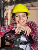 Female Engineer Leaning On Forklifts Steering Wheel — Stockfoto
